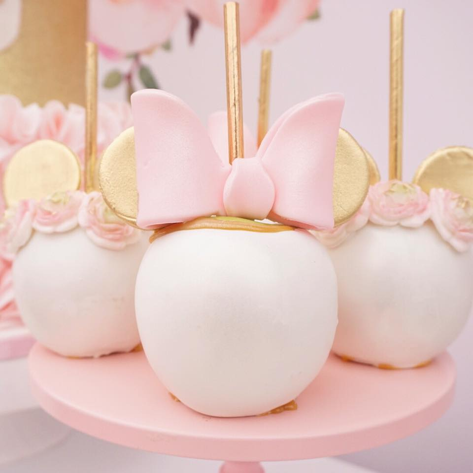 This Minnie Mouse carmel apples. Minnie Mouse birthday party is pink and gold with floral accents and Disney ears. Crazy cute 1st birthday inspiration.