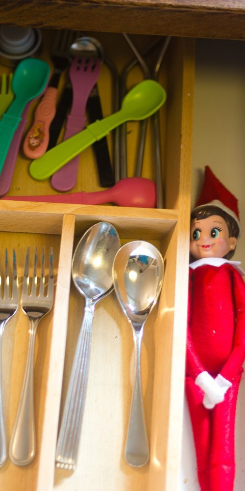 This Elf on the Shelf is hiding in the utensil drawer